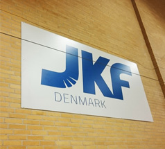 Halskilt til JKF Danmark, med hvid baggrund og blå skrift