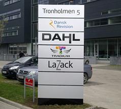 Pylon til flere forskellige virksomheder, med grå baggrund