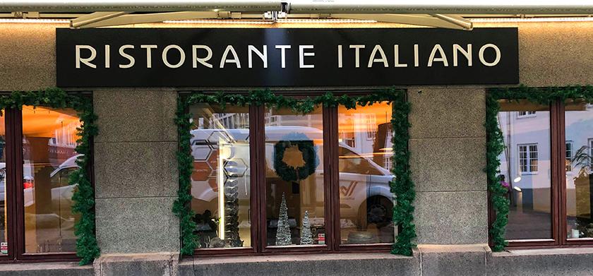 Ristorante italianos facadeskilt, med sort baggrund og hvid skrift.
